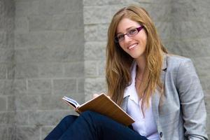 kluge junge Frau, die ihr Tagebuch liest foto