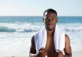 Afroamerikanermann, der am Strand mit Handtuch steht foto