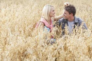glückliches liebendes junges Paar, das sich inmitten des Feldes entspannt foto