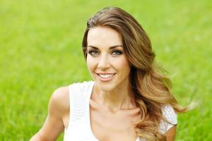 junge Frau im weißen Kleid, das auf Gras liegt foto