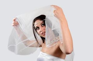 schöne Braut, die Schleier hebt und aufschaut foto