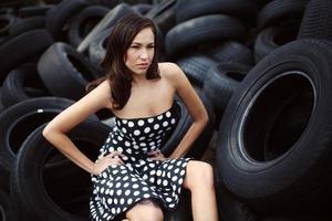 brünette Schönheit sitzt auf Reifenhaufen foto