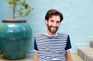 freundlicher junger Mann sitzt und lächelt foto