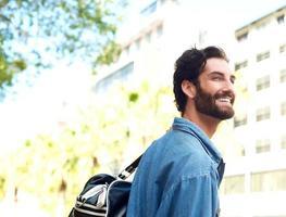 glücklicher lächelnder junger Mann, der draußen mit Reisetasche steht foto