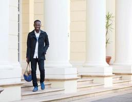glücklicher Mann, der außerhalb des Hotels mit Tasche geht foto