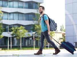 lächelnder junger Mann, der mit Koffer und Tasche reist foto