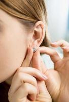 Nahaufnahmeaufnahme der jungen Frau, die Irren mit Diamant trägt foto