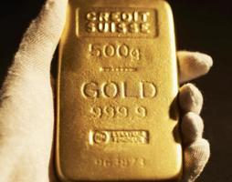 Frauenhand hält Goldbarren