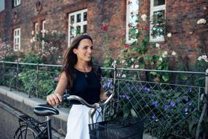 Frau mit dem Fahrrad, das die Straße entlang geht foto