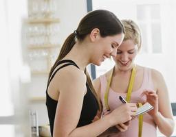 Frau schreibt das Gewicht eines Freundes in ein Notizbuch foto