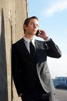 attraktiver Geschäftsmann, der auf Handy draußen spricht foto