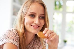 Frau isst Ingwerplätzchen, um Übelkeit der morgendlichen Übelkeit zu stoppen foto