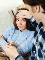 Mann kümmert sich um Freundin, die hohe Temperatur hat foto