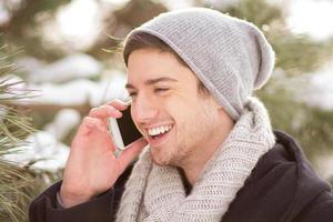 junger Mann, der über Handy spricht foto
