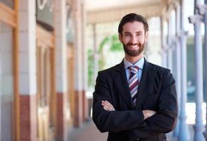 glücklicher Geschäftsmann, der mit verschränkten Armen steht foto