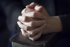 Hände über eine Bibel falten foto