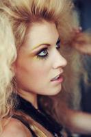 blonde Frau mit großen Haaren und gelbem Lidschatten foto