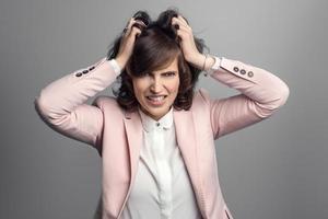 attraktive junge Frau, die an ihren Haaren reißt foto