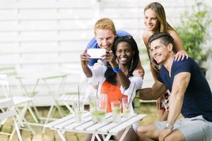Gruppe von Freunden, die einen Tisch sitzen und lächelnd sprechen