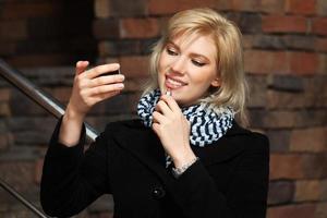 glückliche junge Frau, die einen Lippenstift hält foto