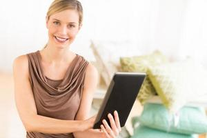 glücklicher weiblicher Besitzer mit digitaler Tablette im Bettwarengeschäft foto
