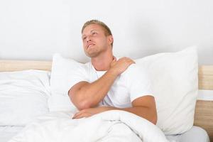 junger Mann, der unter Schulterschmerzen leidet foto