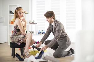 Kundin, die Schuhe mit einem Verkäufer versucht foto