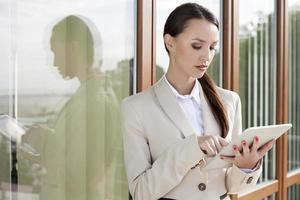 junge Geschäftsfrau, die digitales Tablett gegen Bürogebäude verwendet