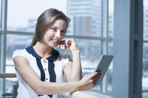 nachdenkliche Geschäftsfrau lächelt an der Kamera, die digitales Tablett hält foto