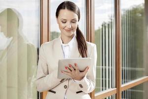 schöne Geschäftsfrau mit digitalem Tablet gegen Bürogebäude