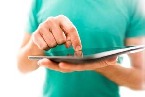 junger Mensch, der eine Tablette navigiert foto