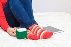 sitzender junger Mensch mit Tasse und Tablette PC