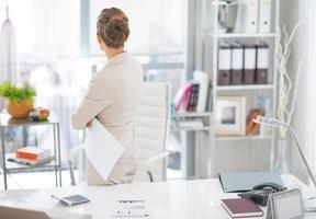 Geschäftsfrau, die mit Dokument im Amt steht. Rückansicht foto