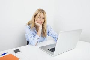 gelangweilte junge Geschäftsfrau mit Laptop am Schreibtisch im Büro foto