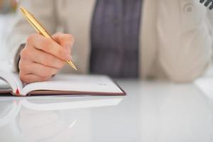 Nahaufnahme auf Geschäftsfrau, die im Tagebuch schreibt foto