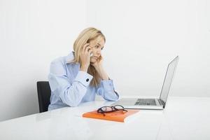 junge Geschäftsfrau, die Handy im Büro beantwortet foto