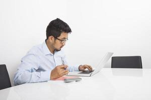 junger Geschäftsmann, der Laptop im Büro benutzt foto