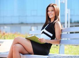 junge berufstätige Frau, die auf einer hölzernen Bank im Park sitzt
