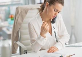 moderne Geschäftsfrau, die Telefon im Büro spricht foto