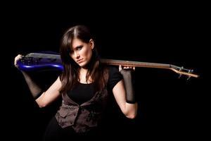 hartes Rocker-Mädchen, das Bassgitarre hinter ihrem Hals hält