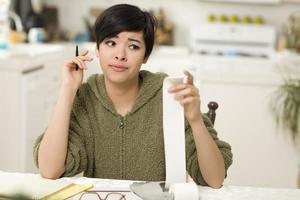 multiethnische junge Frau quält sich mit finanziellen Berechnungen foto