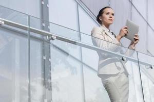 schöne junge Geschäftsfrau, die Tablet-Computer am Geländer des Büros hält foto
