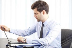Porträt des jungen Geschäftsmannes mit Laptop foto
