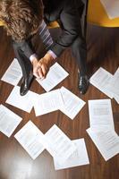 Geschäftsmann mit gefalteten Händen, die Dokumente betrachten, die auf verstreut sind foto