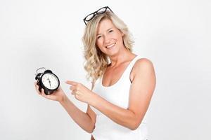 schöne blonde erwachsene Frau, die eine Uhr, Wecker hält. foto