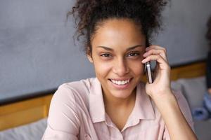 glückliche junge Frau, die auf Handy spricht foto