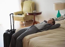 müde Geschäftsfrau, die auf Bett im Hotelzimmer liegt foto