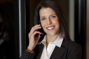 schöne lächelnde Geschäftsfrau, die auf einem Handy spricht foto