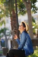 schöne junge Frau, die Musik auf Handy hört foto