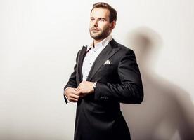eleganter junger hübscher Mann im klassischen schwarzen Kostüm.